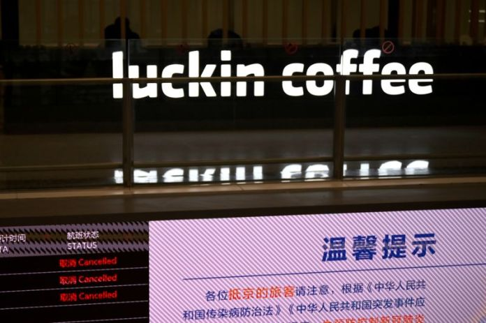 © Reuters. FILE PHOTO: Sign of Luckin Coffee is seen behind an information board showing cancelled flights, at the Beijing Daxing International Airport, as the country is hit by an outbreak of the novel coronavirus, in Beijing