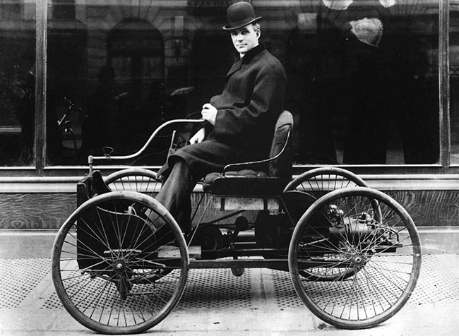 Henry Ford sits in his first automobile, the Quadricycle, in 1896. The machine was a simple four-horsepower engine attached to the frame of a horse buggy and mounted on four bicycle wheels.