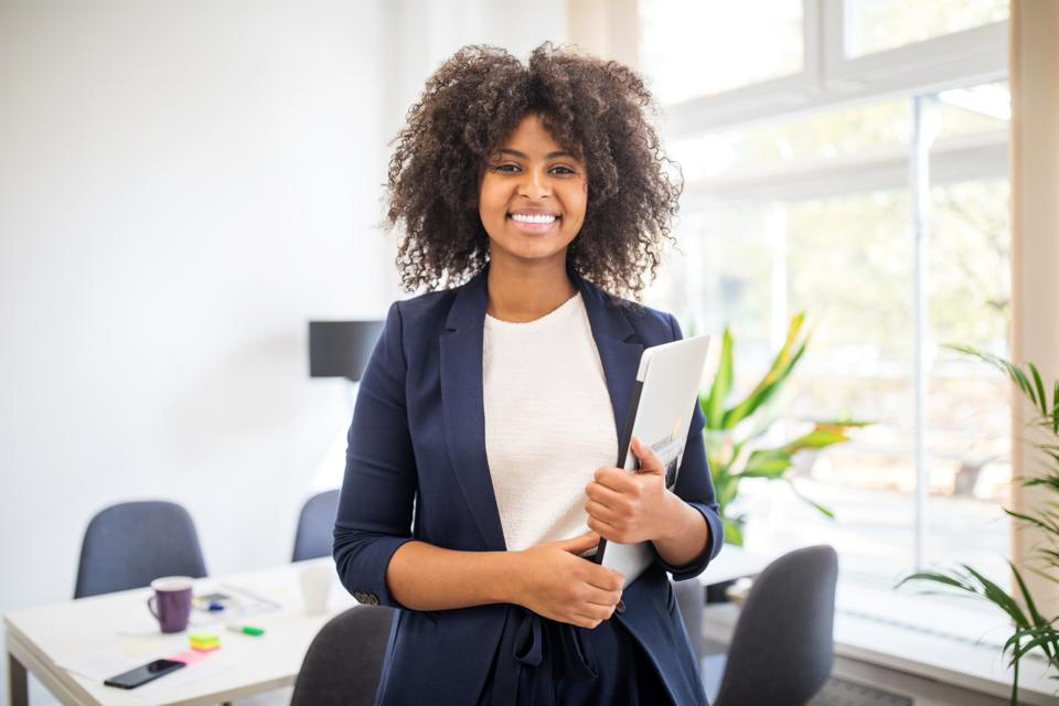 A young woman intern smiles holding a folder in an office.