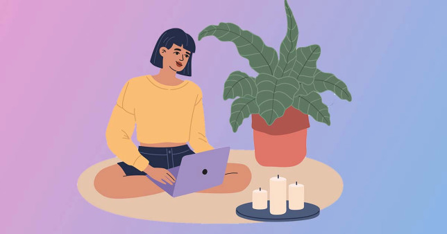 woman working from home on laptop, sitting on floor next to plant