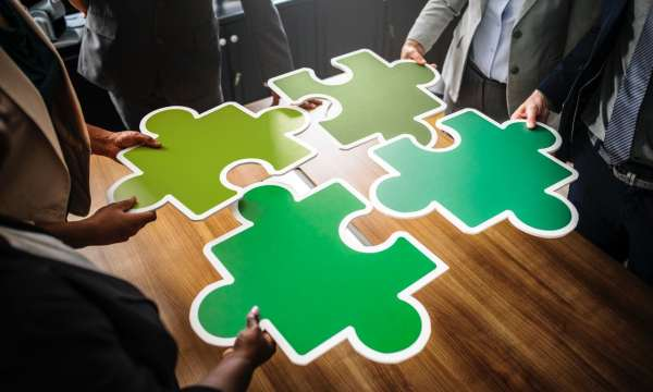 business men fitting green puzzle pieces together