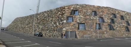 Der Basalt, der abgetragen werden musste, wurde in der Außenmauer des Stadions wiederverwendet. Die Fenster gehören zu den Apartments für die Sportler.