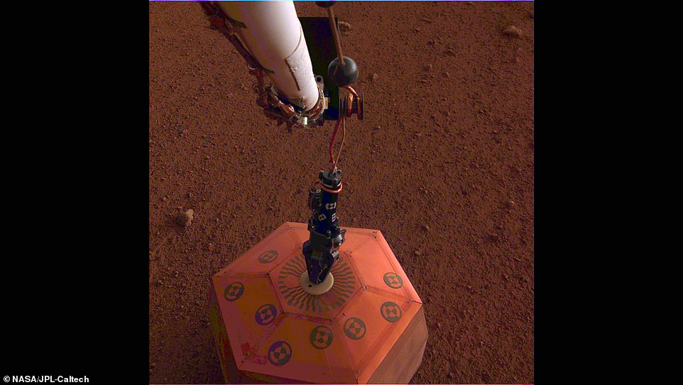 New images from the lander show the seismometer on the ground, after it was lifted onto the surface by the lander's robotic arm.It will record the waves traveling through the interior structure of the planet, and could help explain mysterious 'marsquakes' scientists believe occur regularly.This was the first time a science instrument had ever been placed onto the surface of another planet.