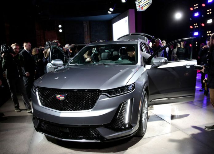 © Reuters. Members of the media look at General Motors 2020 Cadillac XT6 SUV after it was revealed on the eve of press days of the North American International Auto show in Detroit