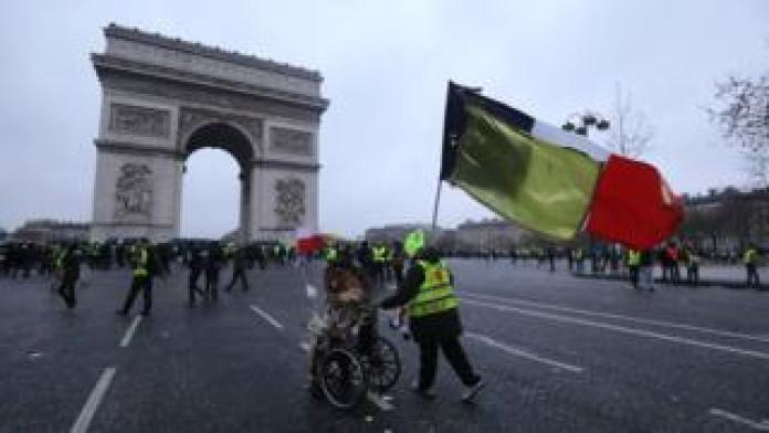 """A demonstrator in a wheelchair is pushed by another, holding a French national flag with a yellow one attached to it, with the Arc de triomphe in the background during a Yellow Vests """"Gilets Jaunes"""" anti-government demonstration in Paris on 12 January 2019"""