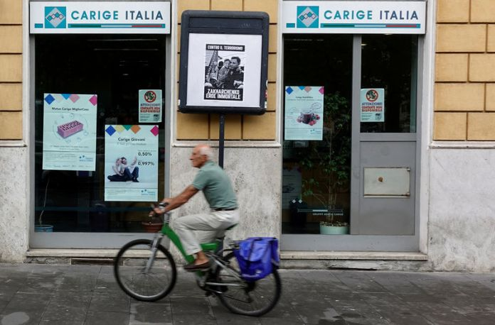 © Reuters. FILE PHOTO: A man rides a bicycle past a Carige bank in Rome