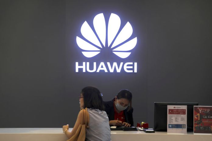© Reuters. A woman sits next to a salesperson at a Huawei shop in Bangkok, Thailand