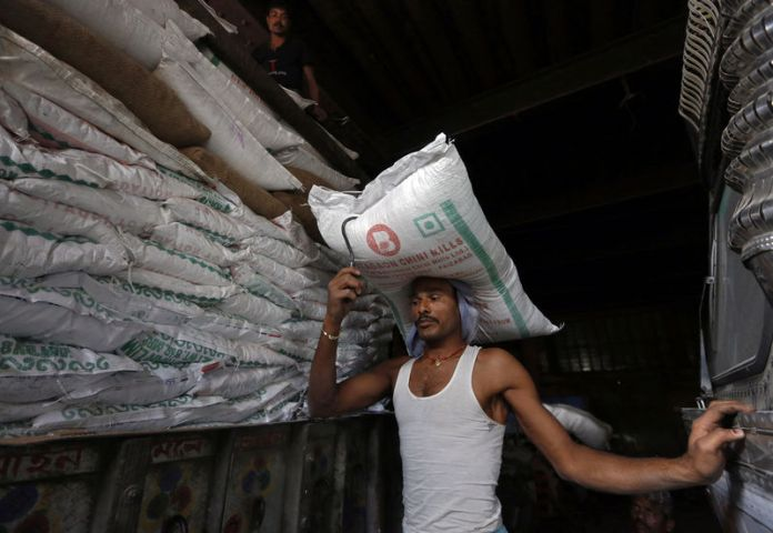 © Reuters. A labourer carries a sack of sugar to load it onto a supply truck at a market area in Kolkata