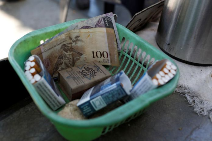 © Reuters. Venezuelan bolivar notes and cigarettes on sale are seen in a basket in downtown Caracas