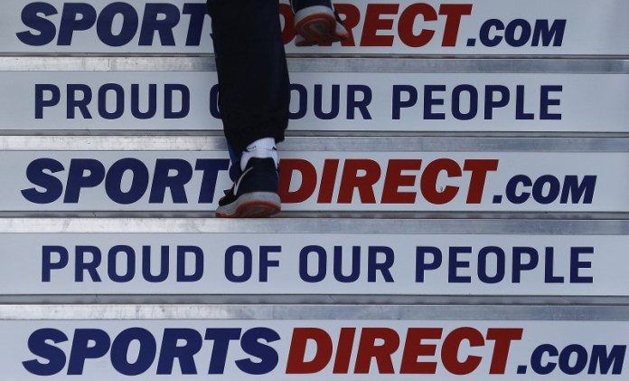 © Reuters. A worker walks up stairs before a Sports Direct general meeting to vote on the re-appointment of chairman Keith Hellawell in Shirebrook