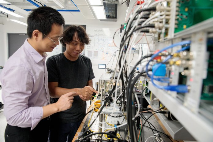 Jia Xu (pictured left) from Trustwave, Singtel's cyber security subsidiary, and Soe Moe Thar (pictured right), a Research Assistant at the Centre for Quantum Technologies at the National University of Singapore (NUS) with some of the hardware being developed for advancing quantum technology at the NUS‐Singtel Cyber Security R&D Lab. (Credit: National University of Singapore)
