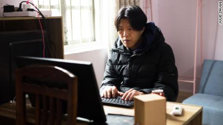 To edit his videos, Wu Nengji uses a old computer with a screen that has no stand and is propped up against a chair.