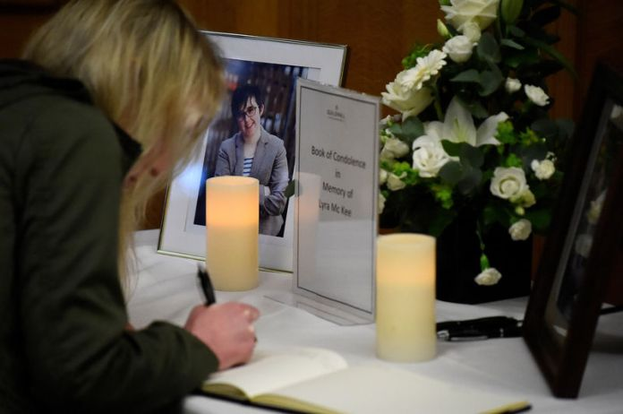 © Reuters. FILE PHOTO: A woman signs a book of condolences in the Guildhall for the 29-year-old journalist Lyra McKee who was shot dead in Londonderry