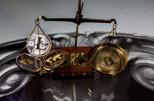 Scale with gold and silver coins that have Litecoin, Bitcoin and ethereum symbols.
