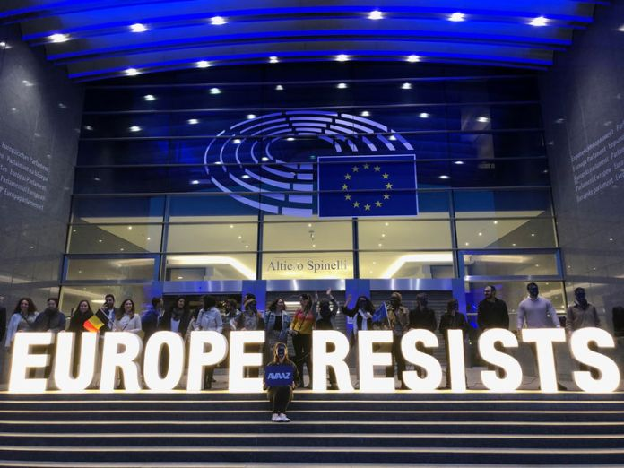 © Reuters. Activists display a banner outside the EU Parliament during the European Elections in Brussels