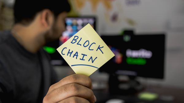 Man sitting at his computer with a sticky note labeled block chain.