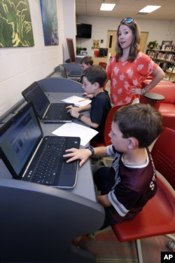 May 8, 2019, photograph, Sharon Stidham, standing, talks to her sons Graham, center, and Miles, front, as they use the laptops at East Webster High School to do homework in Maben, Miss. The internet signal does not reach their house. (AP Photo/Rogelio V. Solis)