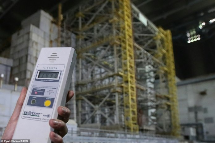 Experts have hired a construction company to undo the work of 600,000 Soviet labourers who started to build the original casing less than two months after the disaster. Pictured: A person using a dosimeter to measure radioactivity next to the older shelter protecting Reactor 4 of the Chernobyl Nuclear Power Plant