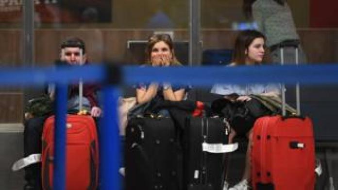Passengers wait near airport check-in counters