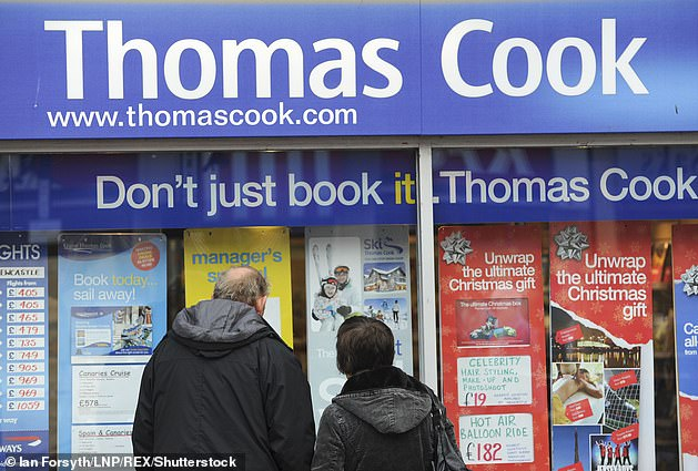 A couple look at holiday offers in the window of a Thomas Cook branch in Redcar. Tens of thousands of customers could be left stranded abroad if the firm goes bust