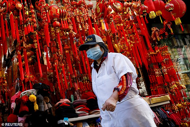 Four people are in isolation in New York being tested for coronavirus - one of which has come back negative and three that are pending. Pictured:A worker wears a mask in Manhattan's Chinatown district of New York City on Friday