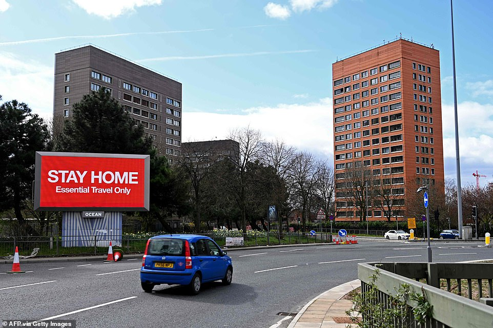 Signs on the side of a road alert motorists to 'Stay Home' and that they should only travel if it is 'Essential', in Manchester. The city has seen a reduction in pollution