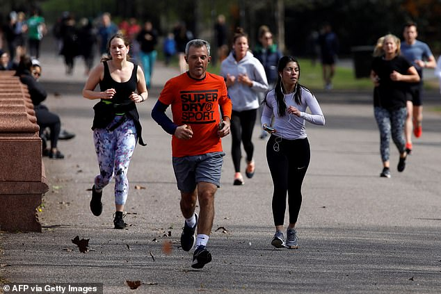 People walk and run to take their daily exercise allowance in Battersea Park in London today as pollution in the city decreases