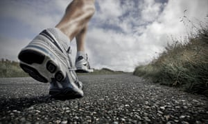 A close, low angle view of a male athlete running along a tarmac road