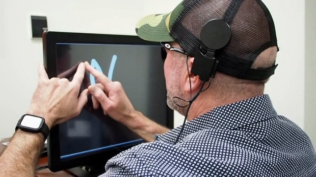 A blind participant drawing letters based on dynamic stimulation to the visual cortex (Credits: Beauchamp et al./Cell / SWNS.COM)