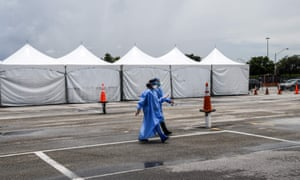 Medical staff wear personal protective equipment kits, including face masks and shields, as they walk near the rapid antigen coronavirus testing site at Hard Rock Stadium in Miami Gardens near Miami, on 5 August 2020.