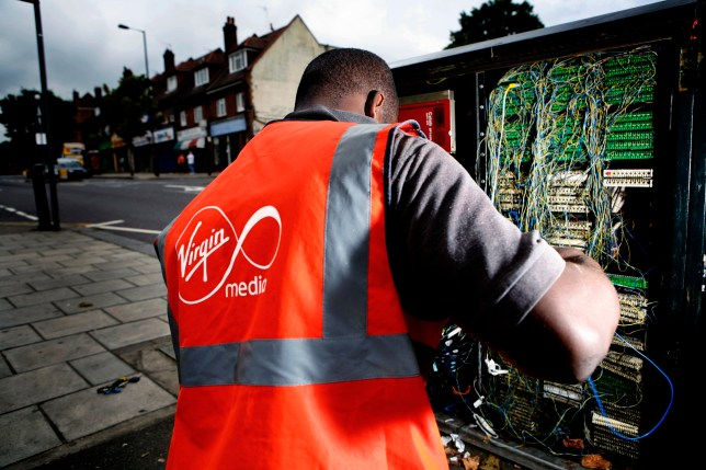A Virgin Media engineer connecting a house to the Virgin telephone, internet and cable television network in North London. (Photo by: Newscast/Universal Images Group via Getty Images)