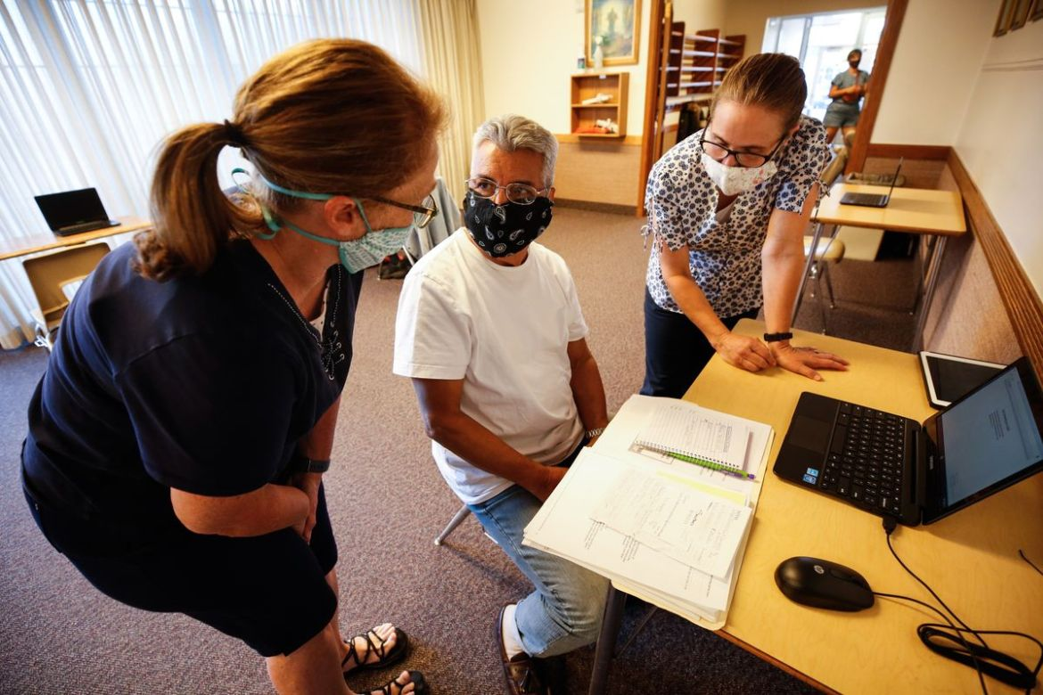 Ann Syphus, left, and Clarrisa Bartholomew, right, help Francisco Terreros use a laptop at Rose Park Stake Center of The Church of Jesus Christ of Latter-day Saints in Salt Lake City on Thursday, Aug. 6, 2020. It is part of a program for people in the community who don't have internet access in their home.
