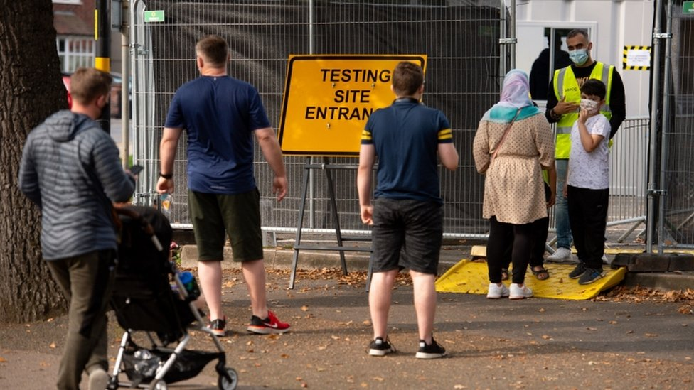 Members of the public queue at a coronavirus testing facility in Sutton Coldfield