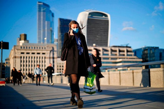 A woman wearing a protective face mask speaks on the phone as she crosses London Bridge in the evening sunshine, in London on September 25, 2020, as new restrictions are introduced to combat the spread of the coronavirus. - Britain has tightened restrictions to stem a surge of coronavirus cases, ordering pubs to close early and advising people to go back to working from home to prevent a second national lockdown. (Photo by Tolga Akmen / AFP) (Photo by TOLGA AKMEN/AFP via Getty Images)