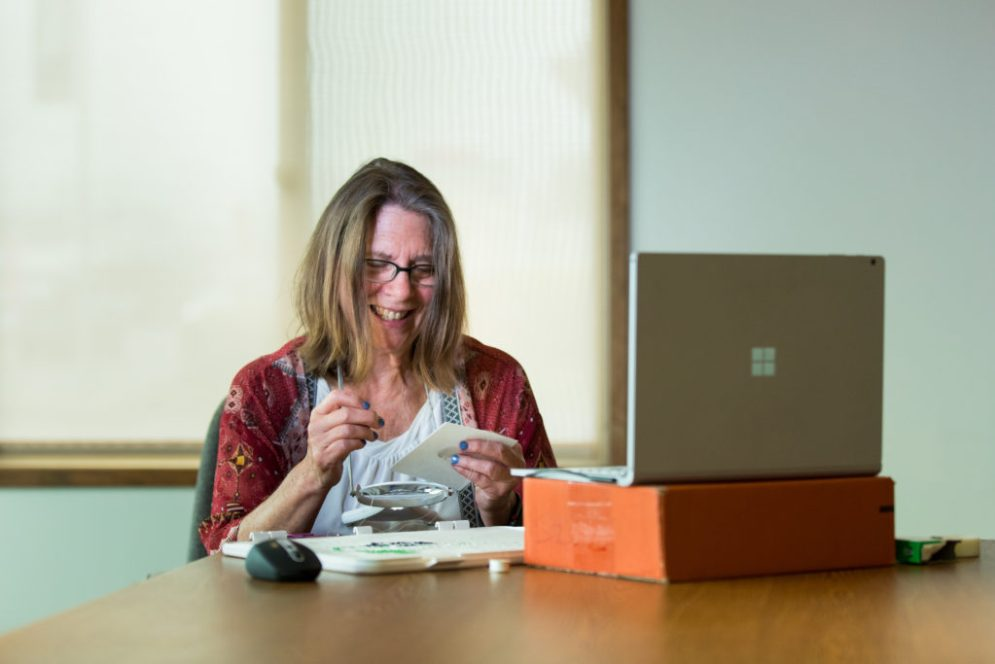 A woman beads while sitting at a table in front of a laptop.