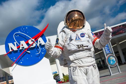 Astronaut in front of NASA logo