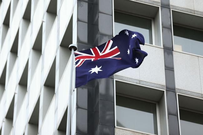 © Bloomberg. The Australian flag flies outside the Reserve Bank of Australia (RBA) headquarters in Sydney, Australia, on Monday, Dec. 4, 2017. Australia's central bank is on track for its longest stretch of unchanged interest rates as it bets a tightening job market will begin to put upward pressure on wages -- at some stage. Photographer: Brendon Thorne/Bloomberg