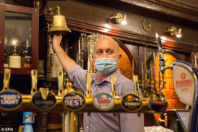 General manager Michael Rogerson rings for last orders in the Horseshoe Bar in Glasgow on Friday before it had to close at 6pm for two weeks