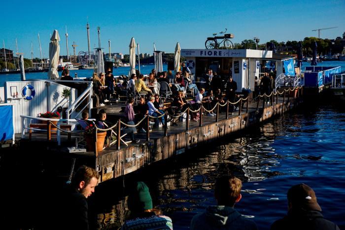 'The same old Stockholm': people socialise aboard a floating bar at Strandvagen, Stockholm, last month