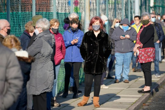 Members of the public queue at a mass Covid-19 testing site in Liverpool