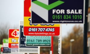 A row of for sale and to let signs stand outside a housing development