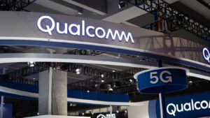 Qualcomm (QCOM) logo on a large sign with another sign that says 5G