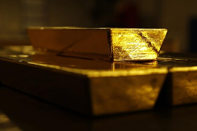 © Bloomberg. Bars of gold bullion sit underneath a 12.5 kilogram gold bar at the Valcambi SA precious metal refinery in Balerna, Switzerland, on Tuesday, April 24, 2018. Gold's haven qualities have come back in focus this year as President Donald Trump's administration picks a series of trade fights with friends and foes, and investors fret about equity market wobbles that started on Wall Street and echoed around the world. Photographer: Stefan Wermuth/Bloomberg
