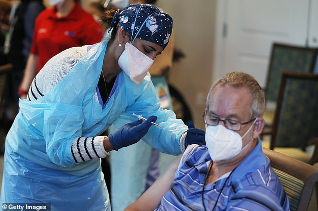 On Wednesday, the HHS announced it would be distributing $22 billion to all 50 states, the District of Columbia and major U.S. cities to help curb the coronavirus pandemic. Pictured: A healthcare worker administers a Pfizer-BioNtech COVID-19 vaccine at the John Knox Village Continuing Care Retirement Community in Pompano Beach, Florida, January 6
