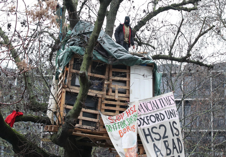 A protester at an HS2 Rebellion encampment in Euston Square Gardens in central London. Picture date: Saturday January 30, 2021. PA Photo. The HS2 Rebellion campaigners, an alliance of groups and individuals campaigning against the planned high-speed railway, claim the small green space near Euston Station will be built over with a temporary taxi rank before being sold to developers as part of plans for the high-speed railway. Photo credit should read: Yui Mok/PA Wire
