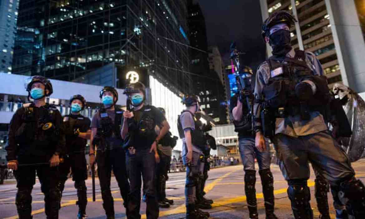 Riot police stand guard on a Hong Kong street to prevent a gathering of pro-democracy protesters.