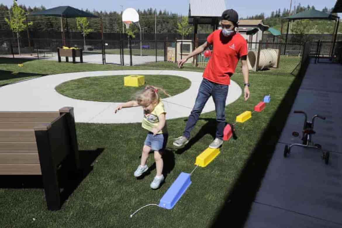 Aaron Rainboth, a teacher at Frederickson KinderCare in Tacoma, Washington, wears a mask while playing outdoors with a child.