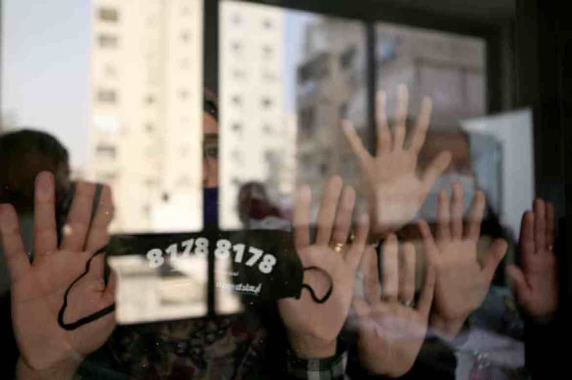 Women in Beirut display a face mask bearing a helpline number