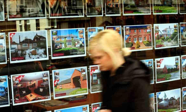 A woman walks past an estate agent's window