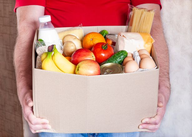 Grocery delivery courier man in red uniform holds cardboard box